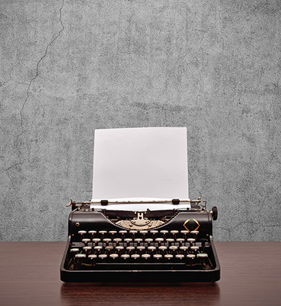 typewriter on a desk in front of concrete wall